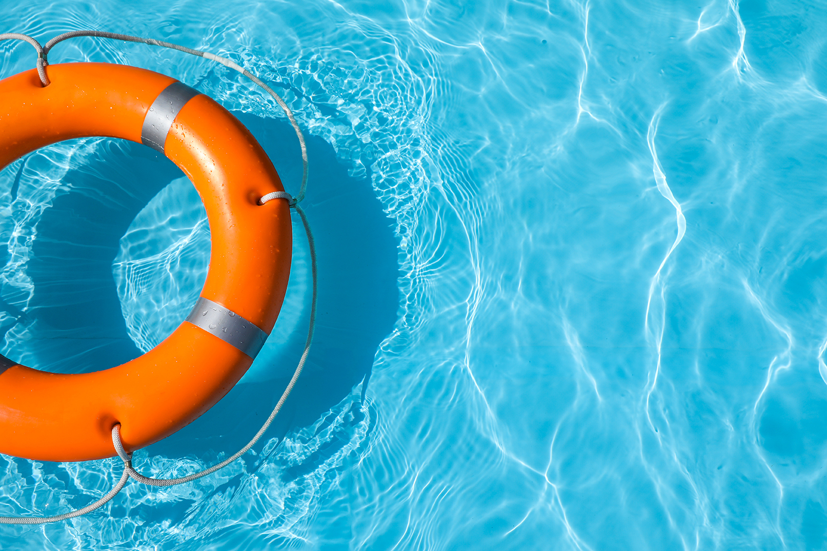 Lifebuoy floating in swimming pool on sunny day.